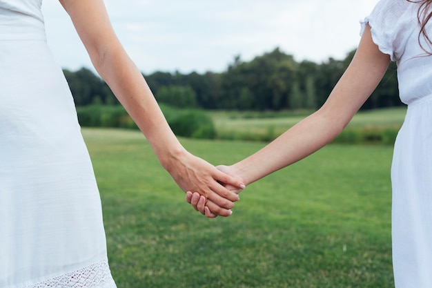 Close up mother and daughter holding hands outdoors