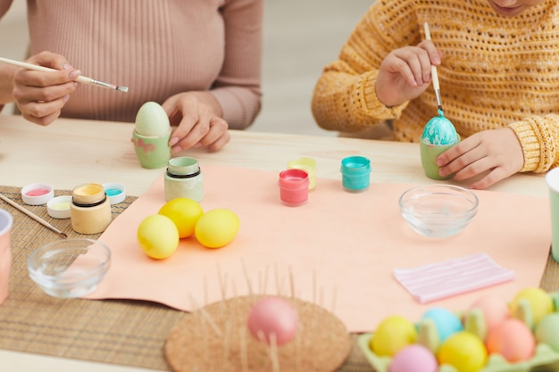 Close up of mother and daughter painting easter eggs pastel color sitting at table in cozy kitchen interior, copy space