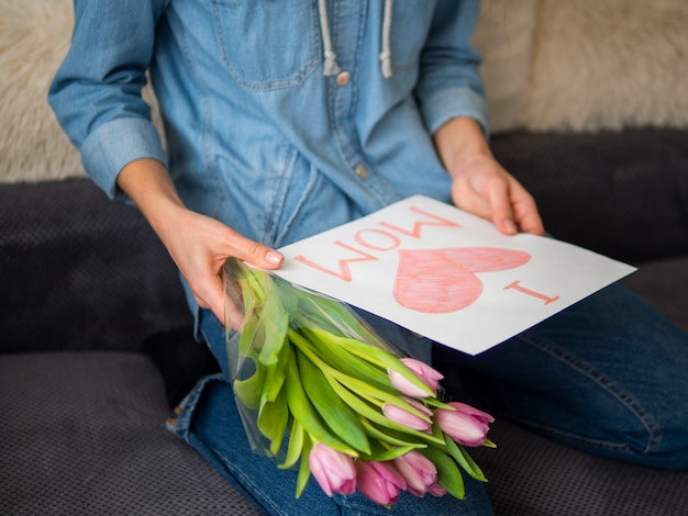 Close-up mother holding drawing and flowers