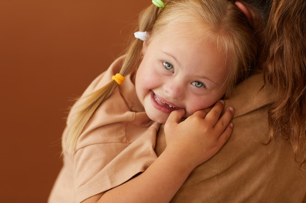 Close up of mother holding happy daughter with down syndrome while standing against plain brown surface in studio