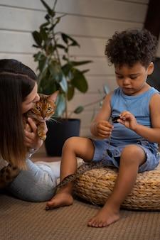 Крупным планом мать, ребенок и кошка в помещении