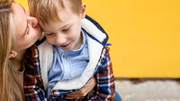 Мать крупным планом, целуя ее маленького мальчика
