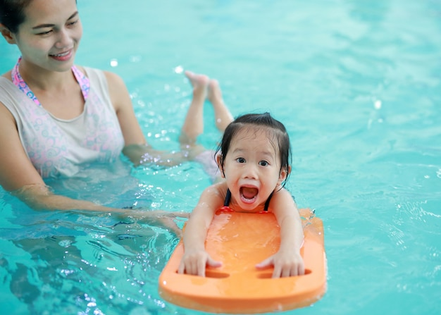 Close up mother teaching kid in swimming pool