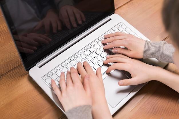 Мать крупным планом учит сына пользоваться ноутбуком