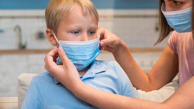 Мать крупным планом учит сына, как носить маску для лица