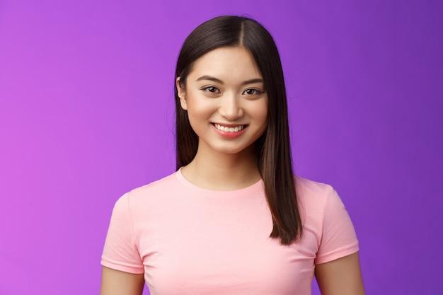 가까이서 동기가 부여된 독단적인 잘 생긴 아시아 여성은 하얀색 완벽한 미소를 짓고, 캐주얼하게 서서 즐거운 대화를 나누고, 낙관적이며, 흥미진진한 긍정적인 분위기의 보라색 배경을 가지고 있습니다.