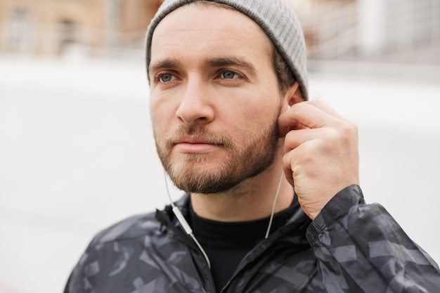 Close up of a motivated young fit sportsman listening to music with earphones while standing at the stadium