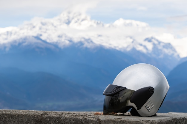 Close up of motorcycle helmet with mountain range on background. free riding, travel on motorbike concept. stock photo.