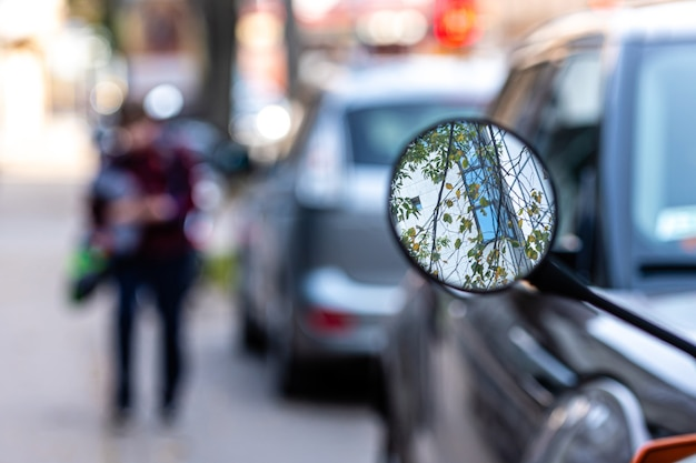 Close-up of a motorcycle mirror parked on the side of the street, soft focus, blurred background