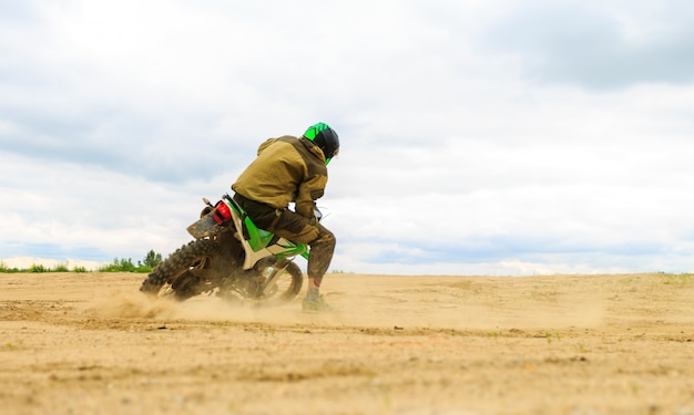 Close-up of mountain motocross race in dirt track in day time.
