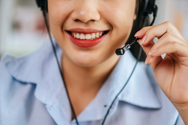 Close-up mouth of cheerful asian woman wear headset smiling during video call stream conference to working online while during quarantine covid-19 self isolation at home, work from home concept