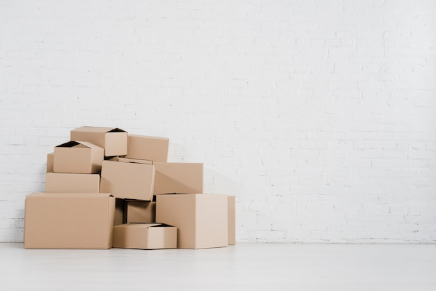 Close-up of moving cardboard boxes standing against brick wall