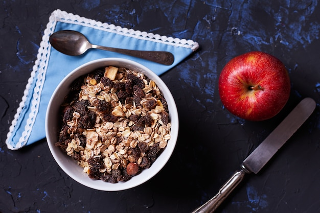 Close up of muesli bowl, and red apple viewed from above