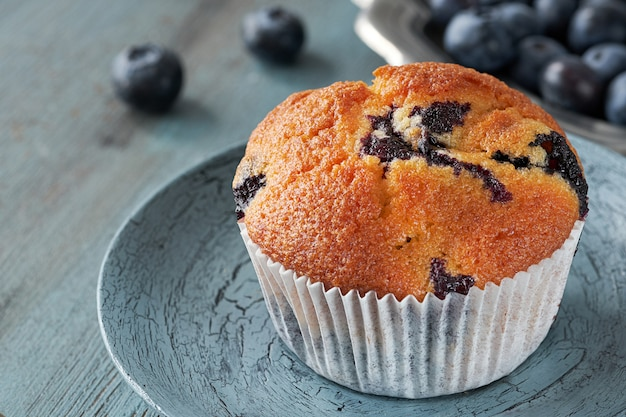 Close up on muffin with blueberries on gray rustic table