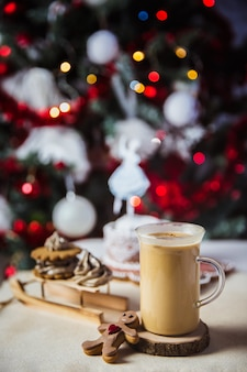 Close up mug with coffee and milk on a wooden table, gingerbread house and christmas lights