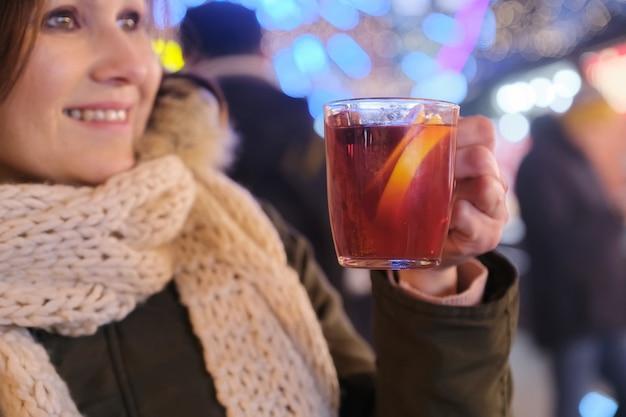 女性の手でグリューワイン、屋外のクリスマスイブニングマーケットの背景とクローズアップマグカップ