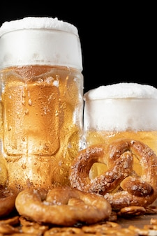 Close-up mugs of beer with foam and pretzels