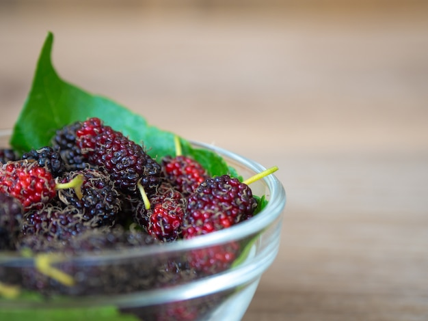 Close up of mulberry with a green leaves in glass bowl on the wooden plate on wooden table.