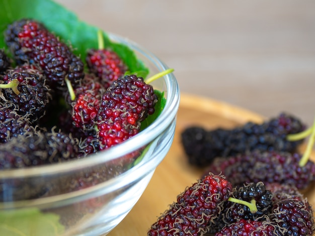 Close up of mulberry with a green leaves in glass bowl