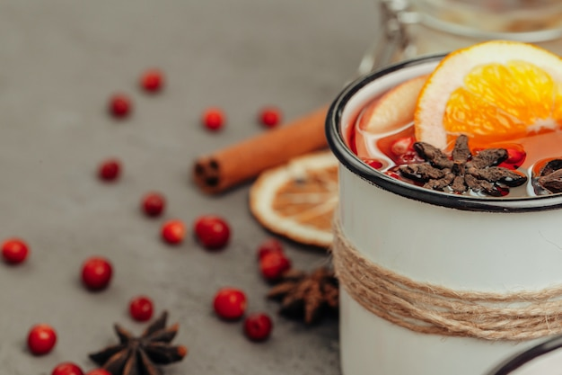 Close up of mulled wine cup with spices and berries on grey table