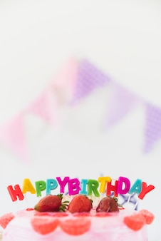 Close-up of multi colored candles and birthday cake