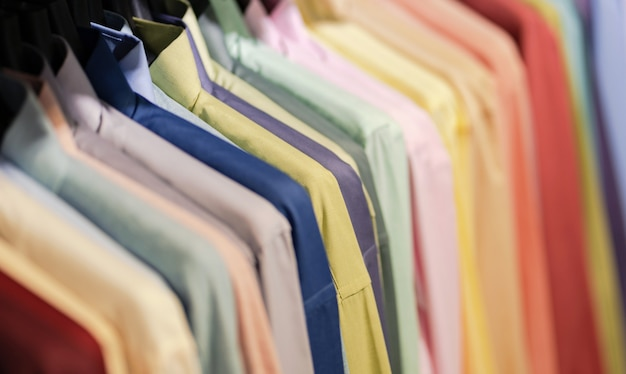 Close up of multi colored shirts on hangers, colorful apparel cloth background