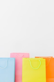 Close-up of multi colored shopping bags on white background