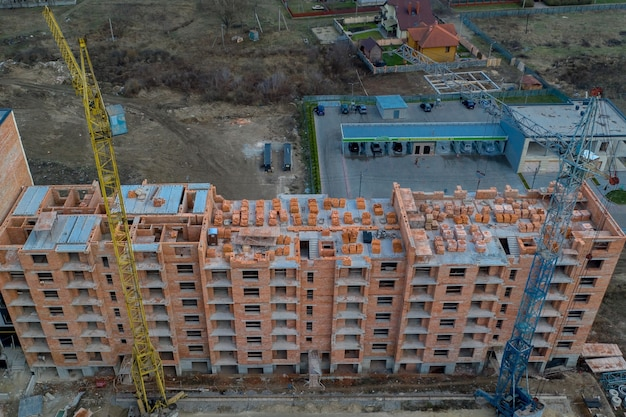 Close-up on a multi-storey residential building under construction from red brick with a part of a crane.