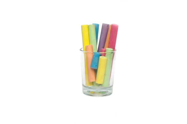 Close up multicolored chalk in glass cup on white background