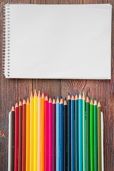 Close-up of multicolored pencil and white spiral note book on wooden desk