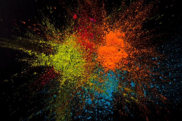 Close-up of a multicolored powder exploding on black surface