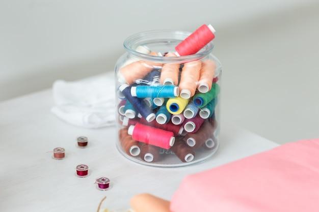 여러 가지 빛깔의 실을 닫고 보빈이 투명한 유리 항아리의 테이블에 놓여 있습니다.