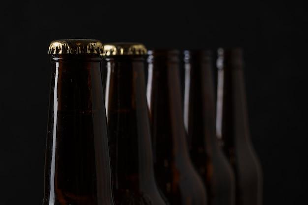Close-up multiple beer bottles aligned