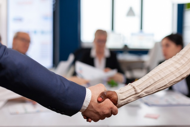 Close up of multiracial business partners standing in front of conference desk shaking hands after signing partnership contract