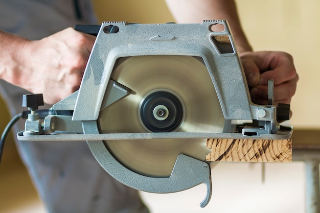 Close-up of muscular carpenter hands using new shiny modern powerful circular sharp electrical saw for cutting hard wooden board. professional tools for construction and building concept.