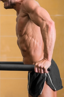 Close up of a muscular man doing triceps dip on parallel bars in gym