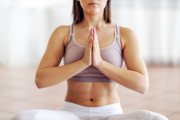 Close up of muscular young brunette sitting in lotus position and meditating.