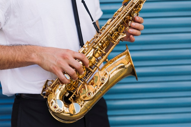 Close up musician holding saxophone
