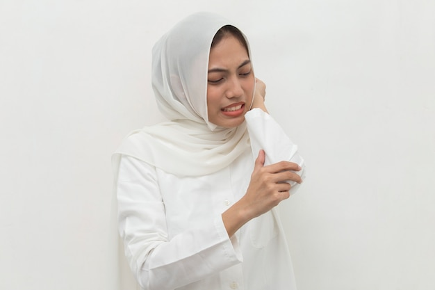 Close up muslim woman having pain in injured elbow hand isolated