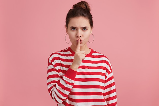 Close up of mysterious girl, demonstrates a gesture of silence, holding an index finger near the mouth calls for privacy to be kept