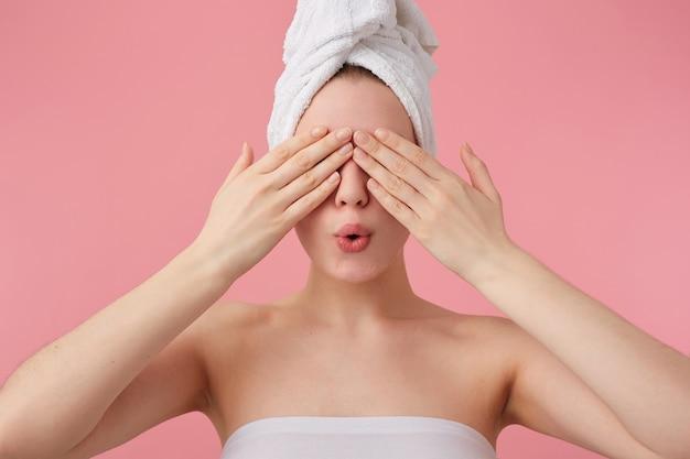 Primo piano di misteriosa giovane donna dopo la doccia con un asciugamano in testa, che copre gli occhi con le mani, in attesa di una sorpresa, si leva in piedi.
