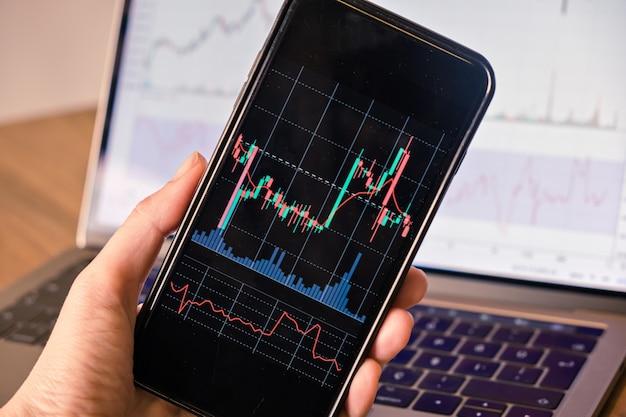 무역 주식 시장 투자 암호에 대한 촛불 그래프와 함께 스마트 폰을 들고 n 손을 닫습니다