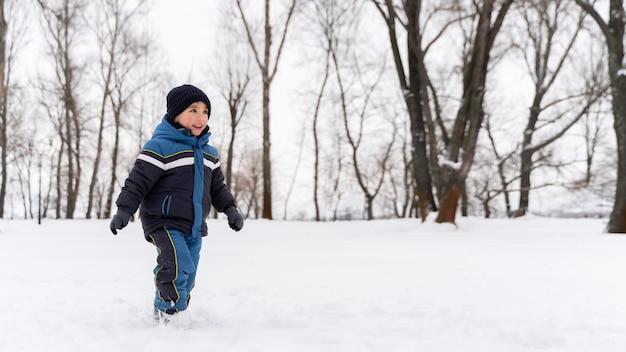 雪の中で遊んでいるn幸せな子供を閉じます