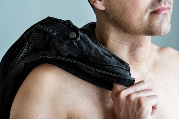 Close up of naked man with his clothes slinging on his shoulder