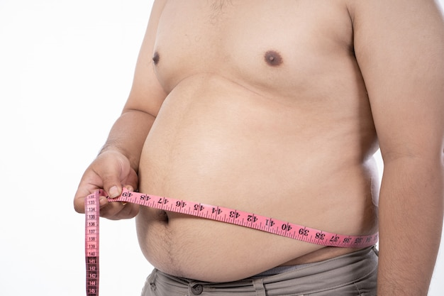 Close up of naked young man measurement his stomach
