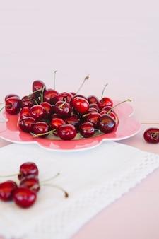 Close-up di tovagliolo e succose ciliegie rosse sul piatto