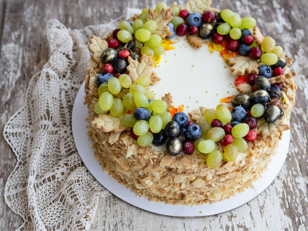 Close-up of napoleon homemade cake is decorated with green and black grapes