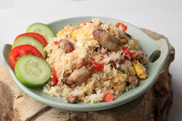 Close up наси горенг cumi asin (жареный рис с солеными кальмарами), приготовленный с чили, пряный и вкусный. типичная индонезийская домашняя еда. подается на зеленой тарелке, изолированной на белом фоне