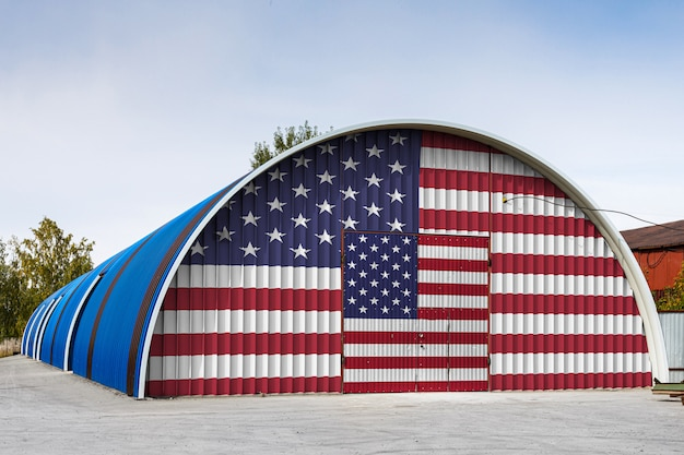 Close-up of the national flag of usa painted on the metal wall of a large warehouse the closed territory against blue sky.