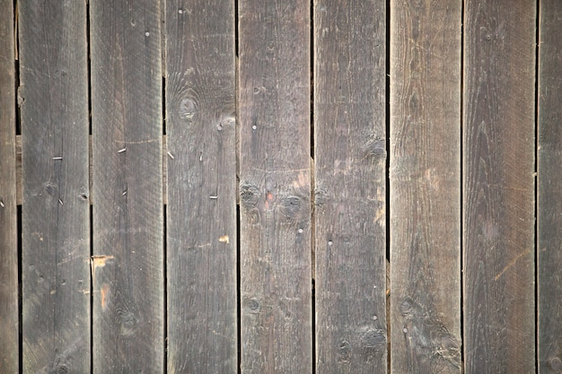 Close-up of natural old vintage weathered gray brown unpainted solid wooden fence or gate of planks and boards. ecological texture vertical copy space sunny crackled background.